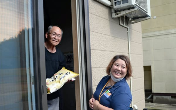 支援のコメを中居知子さん(右)から受け取る田代次雄さん(岩手県山田町)