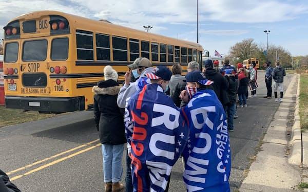 スクールバスへの乗車を待つトランプ支持者(17日、中西部ウィスコンシン州ジェーンズビル)