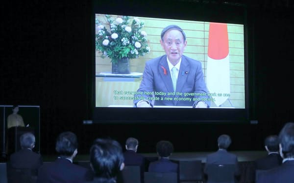 会場に投映された菅首相からのビデオメッセージ(20日午前、東京都中央区)