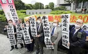 日本郵便訴訟の上告審判決を受け、最高裁前で垂れ幕を掲げる原告ら(15日午後、東京都千代田区)=共同