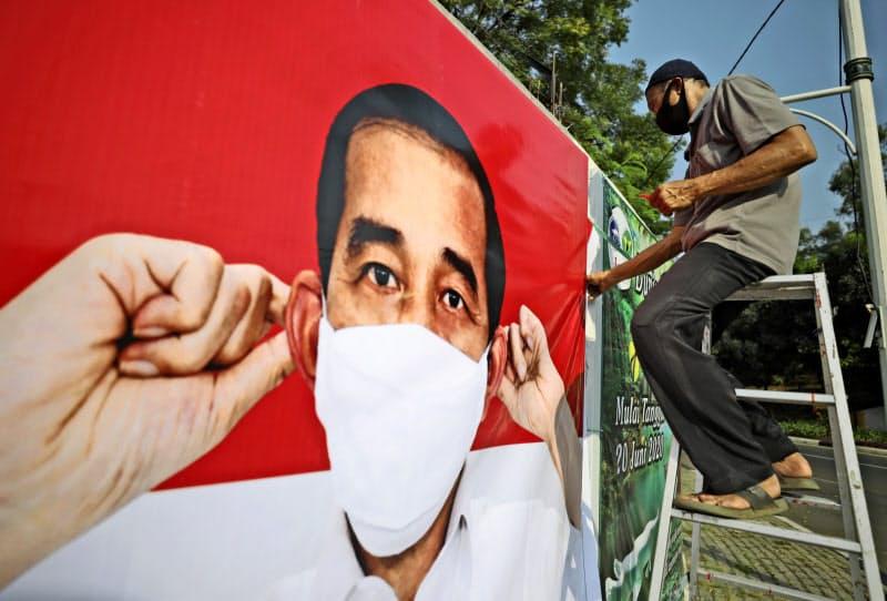 インドネシアのジョコ大統領はマスクの着用を呼びかける自身のポスターを各地で展開する(8月、ジャカルタ)=AP