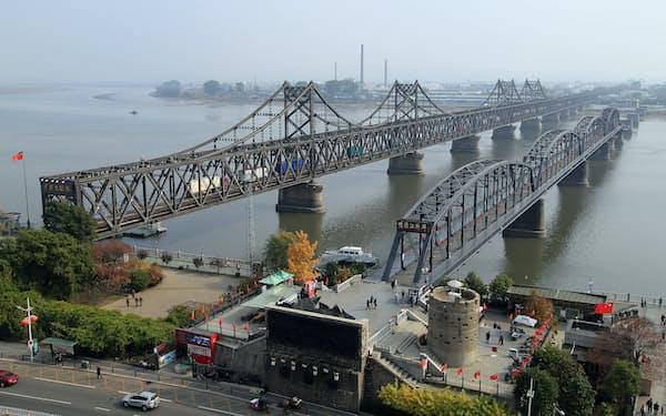 北朝鮮との国境にある「中朝友誼橋」(左)と朝鮮戦争で破壊された「鴨緑江断橋」=17年、中国遼寧省・丹東