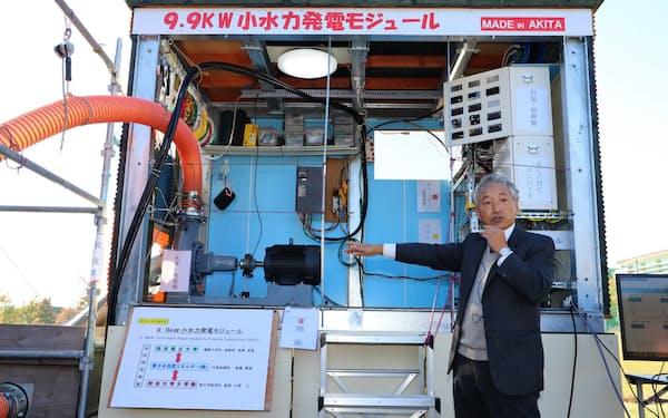小水力発電装置を説明する東日本自然エネルギーの後藤鉄雄社長(20日、秋田県由利本荘市の県立大学本荘キャンパス)