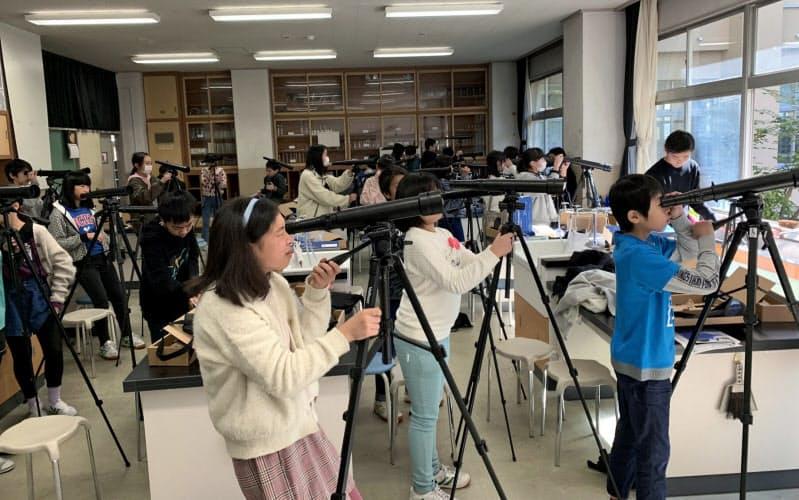 天体望遠鏡を組み立て調整する小学生(松本市立島内小学校提供)