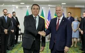 オブライエン米大統領補佐官(右)と握手するブラジルのボルソナロ大統領(20日、ブラジリア)=ブラジル政府提供