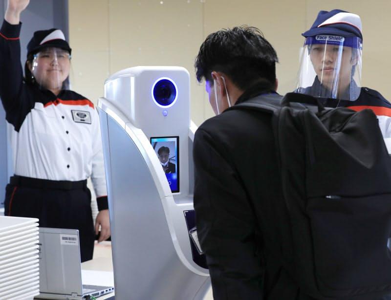 東京五輪の大会関係者の入場検査の実証実験で、顔認証をする関係者役(21日、東京都江東区)