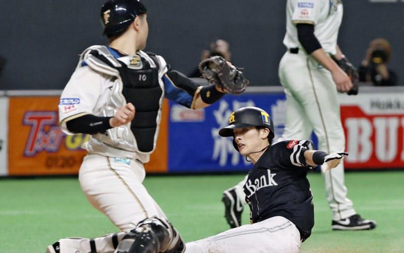 五回ソフトバンク1死三塁、中村晃の右犠飛で周東が勝ち越しの生還。投手バーヘイゲン、捕手清水(21日、札幌ドーム)=共同