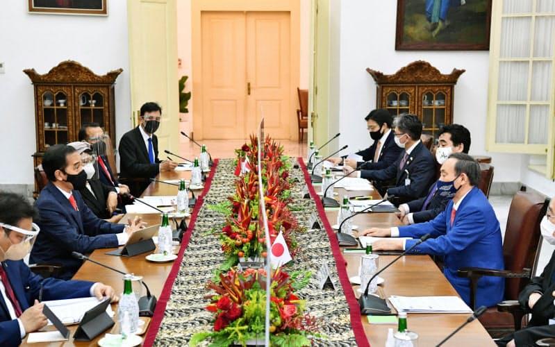 インドネシア・ボゴールの大統領宮殿で、ジョコ大統領(左手前から2人目)と会談する菅首相(右手前から2人目)=(20日、代表撮影・共同)