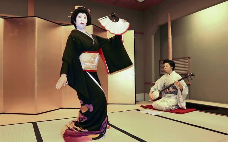 踊りを披露するいち鶴さん(左)と三味線を弾くおり鶴さん(大阪市の「たに川」)=共同