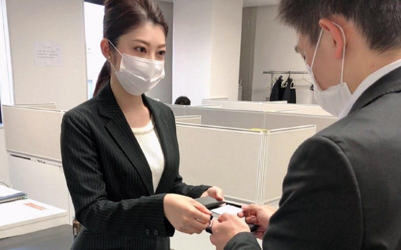 営業先で名刺交換するスターフライヤーの客室乗務員、渕野さん(北九州市、同社提供)