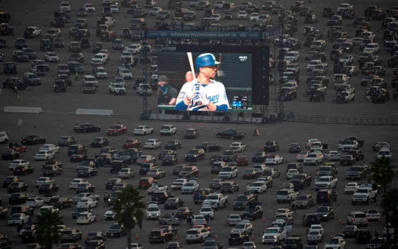 新型コロナの影響で中立地での開催となり、ドジャースファンは本拠地ドジャースタジアムの駐車場に設けられた大画面を見ながら声援を送った=ロイター