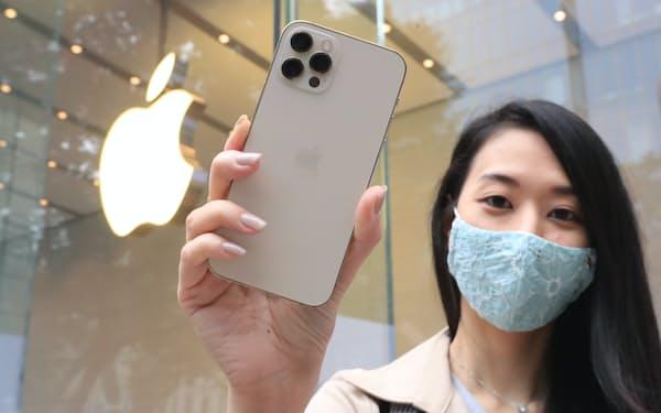 購入したばかりの「iPhone 12 Pro」を手にする女性(23日午前、東京都渋谷区)
