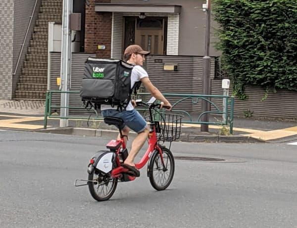 ドコモ・バイクシェアの自転車を使うウーバーイーツの配達員