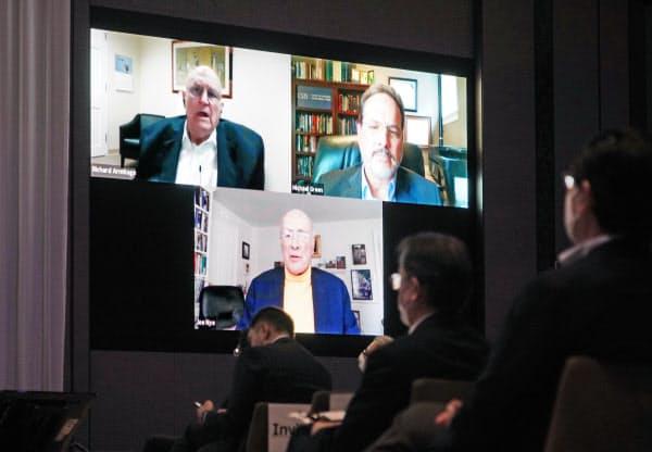 会場に映し出された(左上から時計回りに)アーミテージ、グリーン、ナイの各氏の討論(23日、東京都港区)