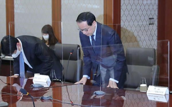 システム障害に関する再発防止策検討協議会の冒頭で謝罪する東京証券取引所の宮原社長(右)(23日、東証)