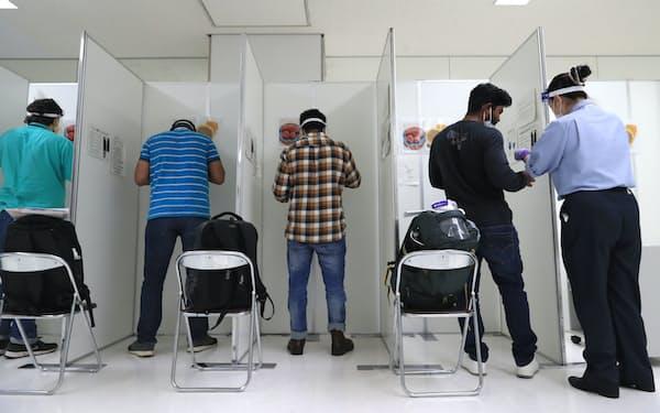 唾液の抗原検査のため、検体を採取する人たち(9月24日、成田空港)