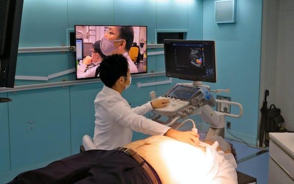 実証実験の様子。5Gで超音波診断画像を伝送し、遠隔から専門医が指示を与える