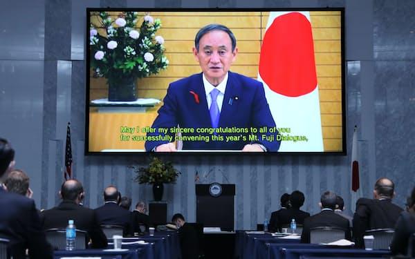富士山会合の会場に映し出された菅首相のビデオメッセージ(24日午前、東京都港区)