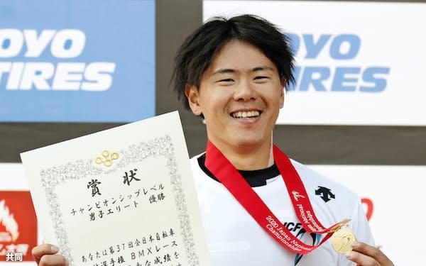 全日本選手権男子で優勝し、表彰を終えて笑顔の長迫吉拓(25日、堺市大泉緑地)=共同