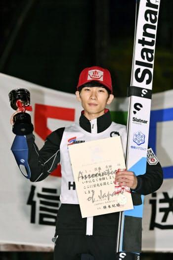 男子ラージヒルで優勝し、表彰式でポーズをとる佐藤幸椰(25日、白馬ジャンプ競技場)=共同