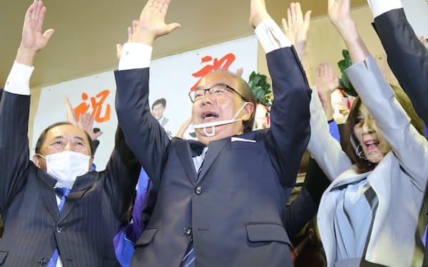 当選確実の一報を受け、万歳三唱する新田氏(中央、25日夜)