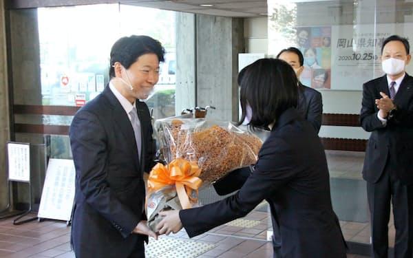 登庁時に職員から花束を受け取る岡山県の伊原木知事(左)(26日、岡山県庁)