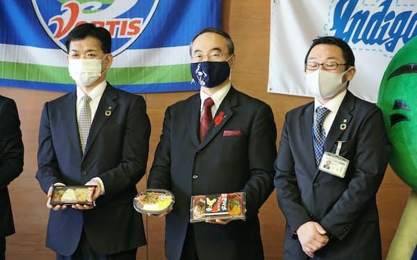 徳島のブランド地鶏を使った弁当を手にする飯泉知事(中)