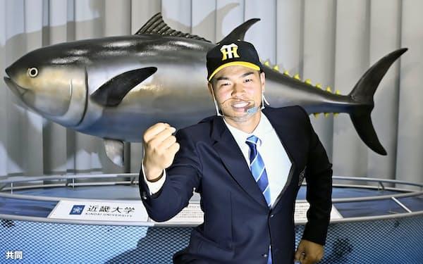 阪神から1位指名され、ポーズをとる近畿大の佐藤輝明内野手(26日、、大阪府東大阪市)=共同