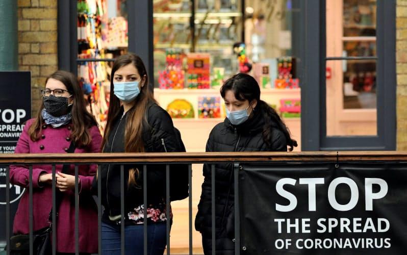 マスクを着用してコベントガーデンを歩く人たち=ロイター