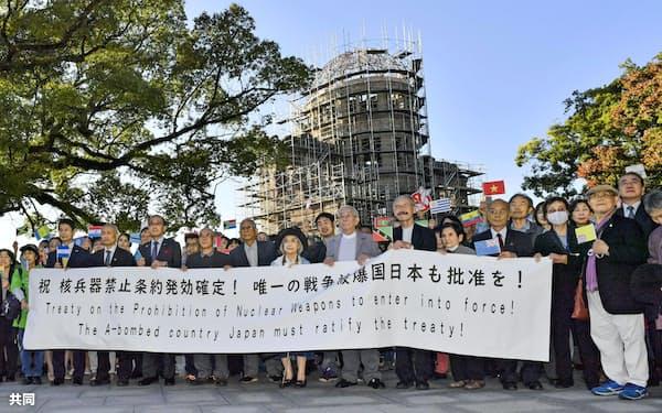 核兵器禁止条約の発効が決まったことを歓迎する人たち(25日、広島市)=共同