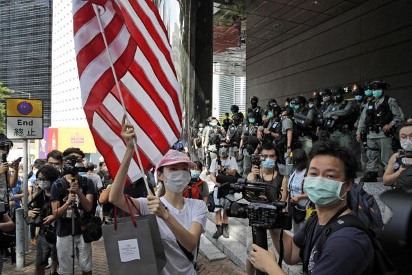 香港の米総領事館の近くで米国旗を掲げる人(7月)=AP
