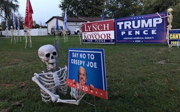 庭先に「不気味なジョー(バイデン候補)にノー」の看板、背後にはトランプ旗を掲げる骸骨の群れも