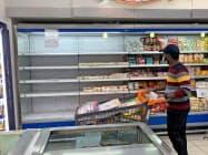 26日、仏製品が棚から撤去されたクウェートのスーパーで買い物をする男性=ロイター