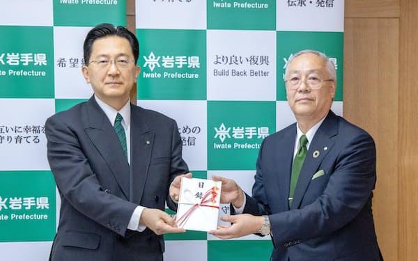 寄付金の目録を達増知事(左)に手渡す田口頭取(28日、岩手県庁)