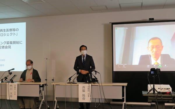 ふるさと納税の仕組みを使ったクラウドファンディングについて説明する京都府の西脇隆俊知事(中)と京都市の門川大作市長(左)。京都大学iPS細胞研究財団の山中伸弥理事長もオンラインで出席した(28日、京都市の京都経済センター)
