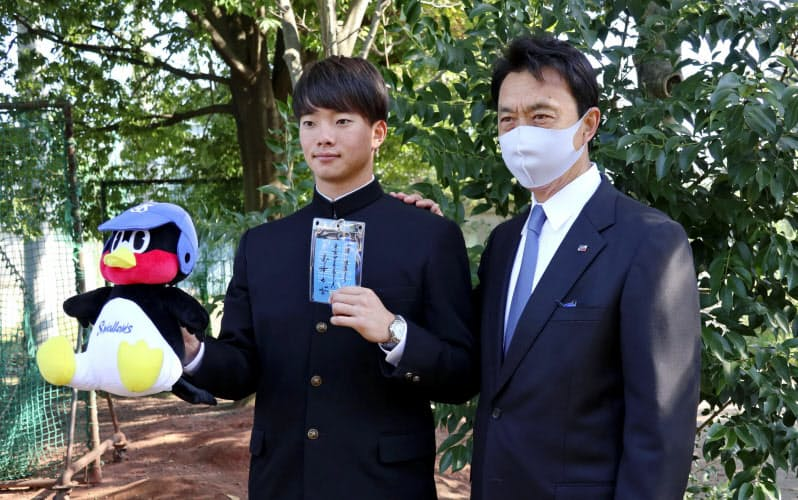 ヤクルトからドラフト1位の指名あいさつを受け、小川GM(右)と写真撮影に応じる慶大の木沢尚文投手(29日、横浜市)=共同