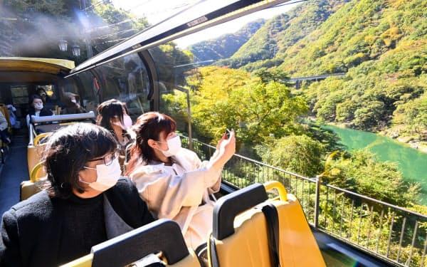 鬼怒川沿いを進むバス(24日、栃木県日光市)