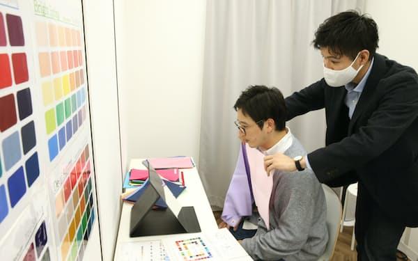 筆者(左)に異なる色の布を当てて似合う色を見つける色彩診断士の桐本さん(横浜市のユースタイリング)=三浦秀行撮影