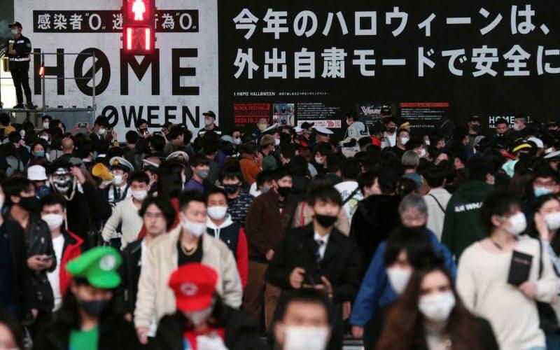ハロウィーンを迎えた渋谷駅前のスクランブル交差点。自宅で過ごすよう促す看板が掲げられた(31日、東京都渋谷区)