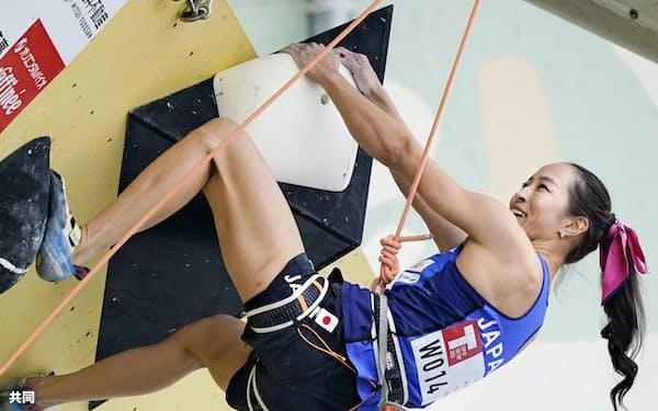 リードの女子決勝で完登し笑顔の野口啓代。ただ一人の完登で優勝した(1日、石鎚クライミングパークSAIJO)=共同