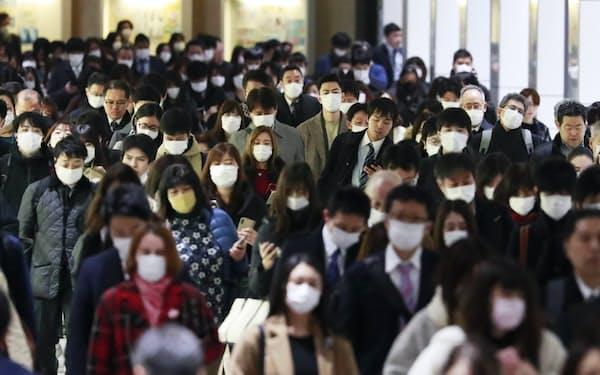 マスク姿で出勤する人たち(3月、東京都新宿区)