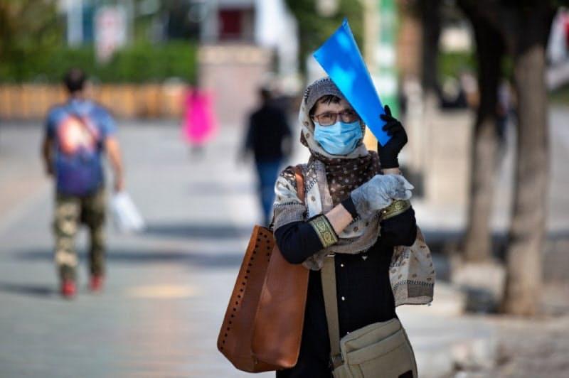 イランには感染「第3波」が到来(テヘランで手袋とマスク姿で歩く女性)