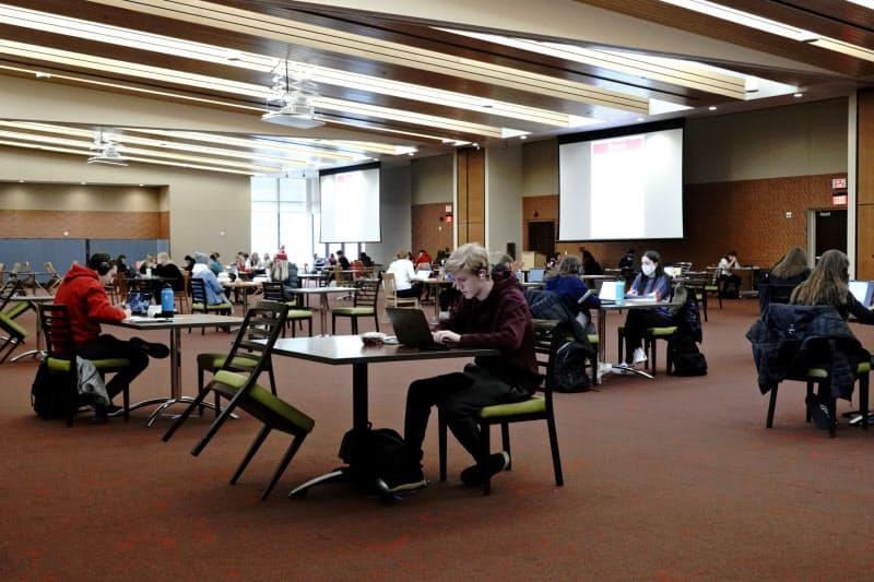新型コロナウイルスの拡大を受けて、距離を空けて座る米国の大学生たち(10月、ウィスコンシン州)=ロイター