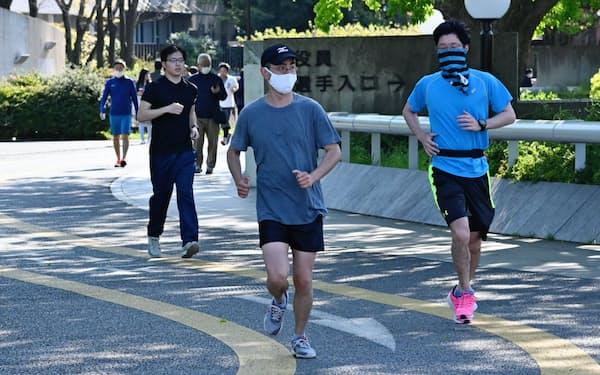 マスク姿でジョギングする人たち(4月、東京都世田谷区の駒沢オリンピック公園)