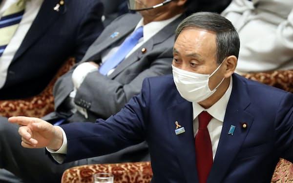 衆院予算委で野党議員の質問に身ぶりで反応する首相(4日)