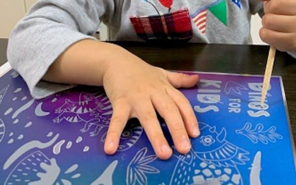 図書印刷は表面を削って色を出す「スクラッチアート」で製造コストを削減できる製造方法を開発した
