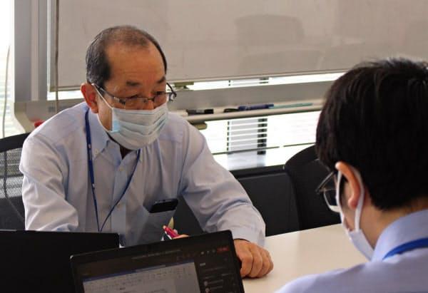 アジア拠点と結んだテレビ会議で話し合う希代博文さん(10月14日、東京都品川区の明電舎本社)