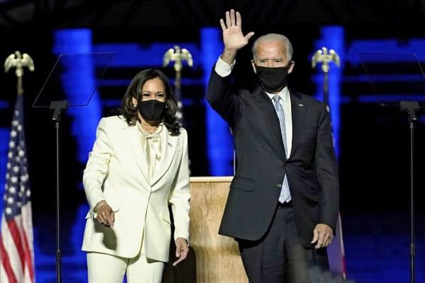 ステージから支持者に手を振るバイデン氏(右)とハリス氏(7日、デラウェア州ウィルミントン)=AP