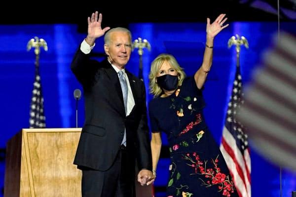 勝利演説後に手を振るバイデン氏(左)とジル夫人(7日、デラウェア州ウィルミントン)=ロイター