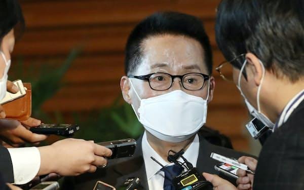 菅首相と会談後、菅首相の著書を手に報道陣の質問に答える韓国国家情報院の朴智元院長(10日)